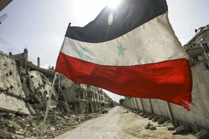 "A Syrian flag flutters outside a military barrack in the devastated Bab Amro neighbourhood of the central restive city of Homs on May 2, 2012. The head of the UN mission to Syria said his observers were having a ""calming effect"" on the ground but admitted the ceasefire was ""shaky"" and not holding.  AFP PHOTO/JOSEPH EID == THIS PICTURE WAS TAKEN ON AN OFFICIAL GOVERNMENT-GUIDED TOUR ==         (Photo credit should read JOSEPH EID/AFP/GettyImages)"
